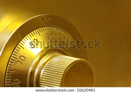 Golden toned combination safe lock, in close-up. - stock photo
