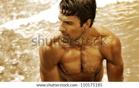 Golden toned fine art portrait of a beautiful muscular young man in the ocean - stock photo