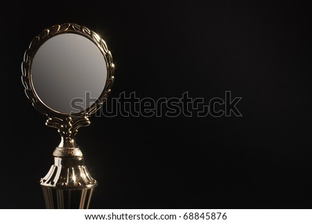 Golden trophy award with laurel wreath against black background with copy space - stock photo
