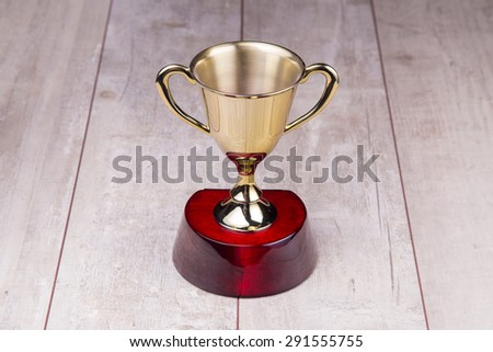 Golden trophy on wood background - stock photo