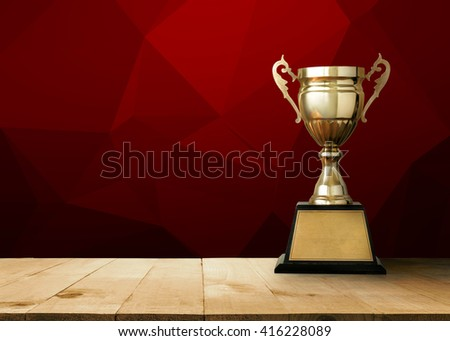 golden trophy on wood table with Red White Polygonal Mosaic Background