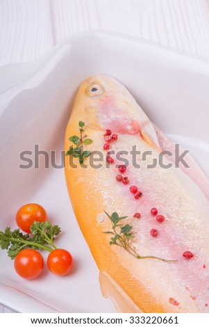 golden trout on a baking dish with cherry tomatoes, red pepper and thyme parsley. gold fish. home kitchen.