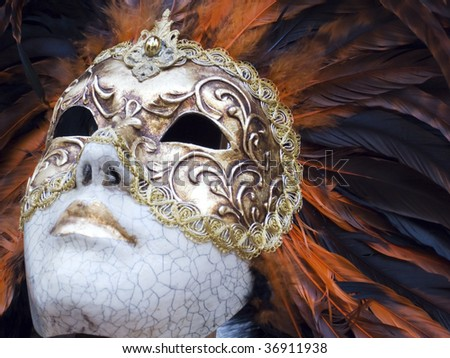 Golden venetian artistic mask with orange and black feathers