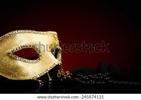 Golden Venice mask and black pearls. Red and black background.