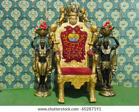 golden vintage luxury throne chair with two egyptian statues - stock photo