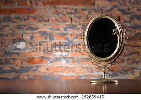 Golden vintage mirror on wood table  - stock photo