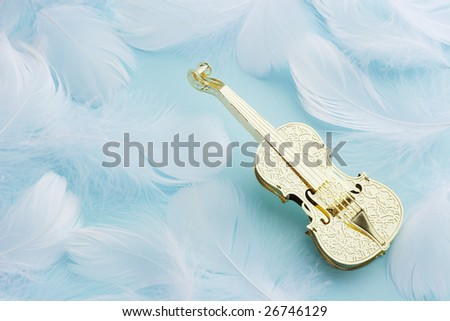 Golden violin with white feather on blue background - stock photo