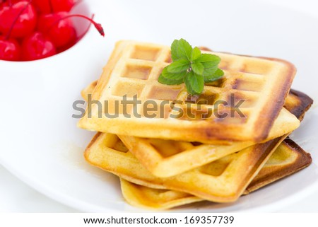 Golden waffle topped with fresh cheery and honey syrup for a delicious dessert - stock photo