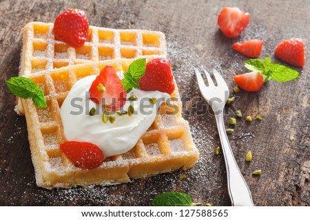 Golden waffle topped with fresh diced strawberries and a dollop of ...