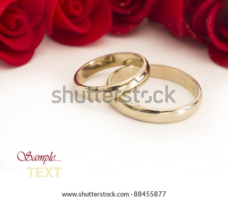 golden wedding rings and red roses - stock photo