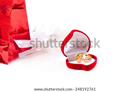Golden wedding rings in open suede box on a white background - stock photo