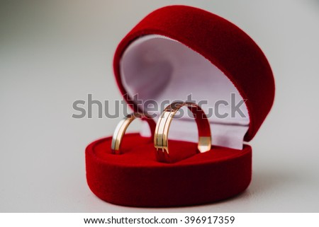 Golden wedding rings in red box the shape a heart