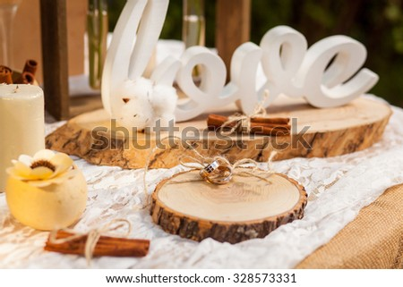 Golden wedding rings lying on wooden stump near candle with flower