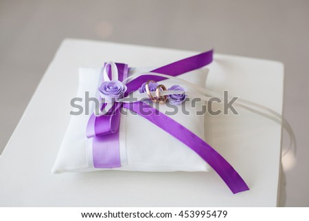 Golden wedding rings on decorated little pillow with purple ribbons - stock photo