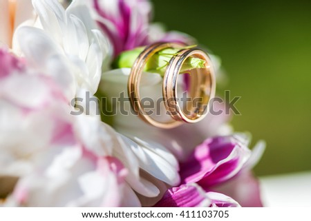 Golden wedding rings on the spring white and purple flowers