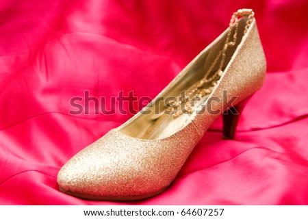 Golden Wedding shoe on red background - stock photo