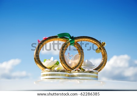 golden weddings rings over car - stock photo