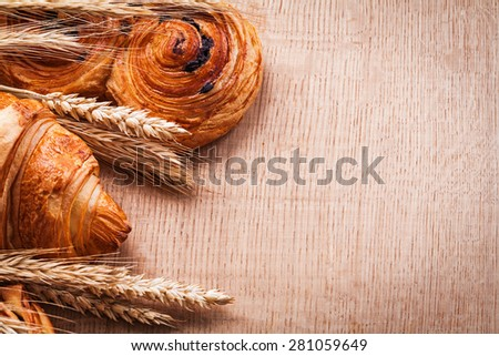 Golden wheat ears croissant bun with raisins on oaken wooden board food and drink concept  - stock photo