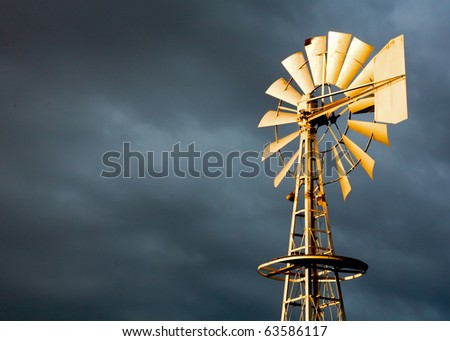 Golden Windmill Illuminated in Light with Stormy Clouds - stock photo