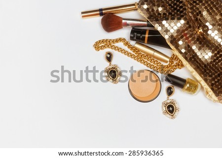 Golden woman accessories. Make up pieces, jewelry and shiny purse. Top view. - stock photo