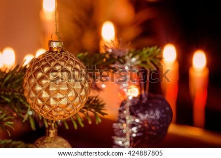 Golden Xmas ball on a tree and Christmas lights - stock photo