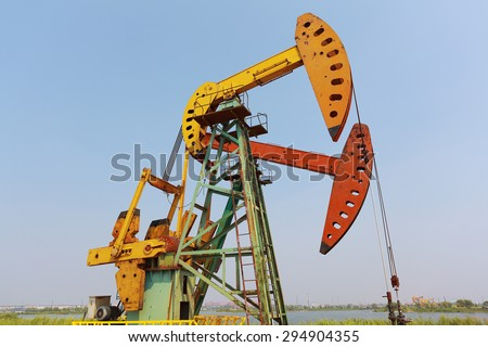 Golden yellow and orange Oil pump oil rig energy industrial machine for petroleum crude - stock photo