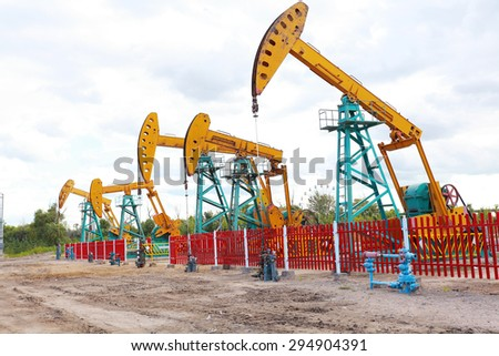 Golden yellow Oil pump oil rig energy industrial machine for petroleum crude of countryside trail dirt road - stock photo