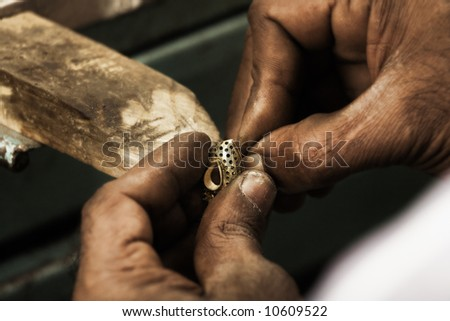 Goldsmith holding an unfinished 22 carat gold earring in his hard working hands. Shallow DOF - focus on earring. Fine gold dust on hands - stock photo