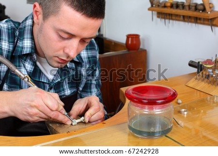 Goldsmith in workshop. Making of jewelery. Handmade. Intentional shallow depth of field. - stock photo