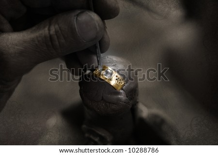 Goldsmith working on an unfinished 22 carat gold ring with big diamond with his hard working hands on grunge paper background - stock photo