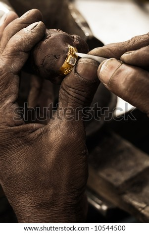 Goldsmith working on an unfinished 22 carat gold ring with big diamond with his hard working hands. Shallow DOF - focus on the ring. Fine gold dust on hands and tools - stock photo