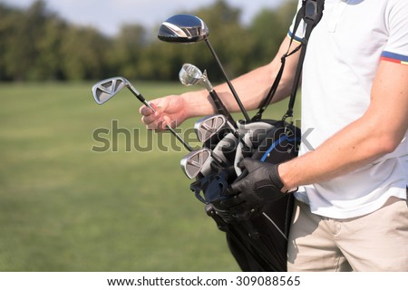 Golf and golfer concept. Man in white T-shirt removing a golf club from his golf bag to start playing professional golf over green course. - stock photo