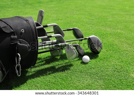 Golf bag with clubs and balls on green field, close up - stock photo