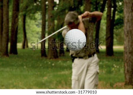 golf ball after leaving tee with man in background - stock photo