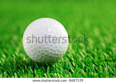 Golf ball against grass background - stock photo