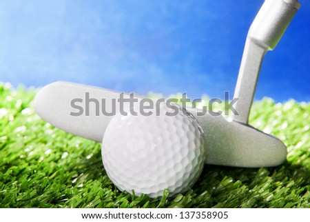 Golf ball and club on green field grass against blue sky - horizontal image - stock photo