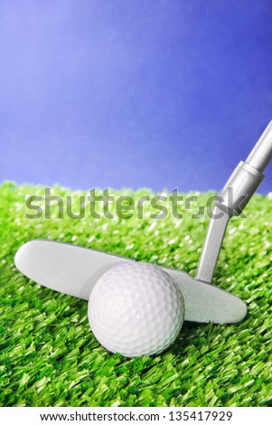 Golf ball and club on green field grass against blue sky - vertical image - stock photo