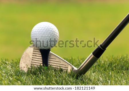 Golf ball and  Driver on green grass background - stock photo