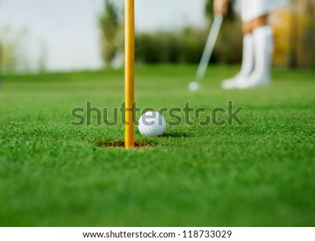 Golf ball and female golfer in background - stock photo