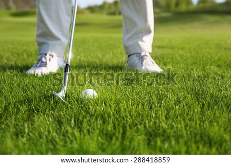 Golf ball and golf club in front of golf player - stock photo