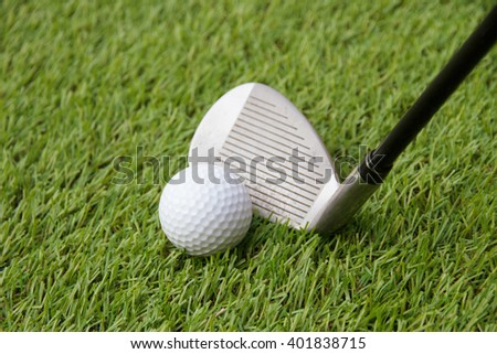 Golf ball and golf club on grass  - stock photo