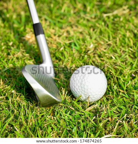 Golf ball and golf club on green glass - stock photo