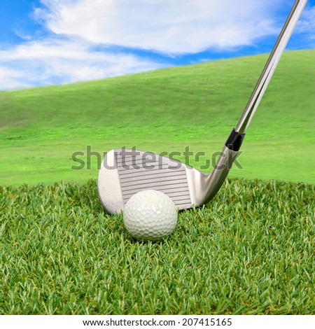 Golf ball and golf club with hill background - stock photo