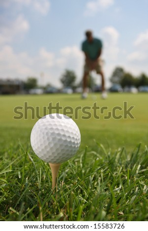 Golf Ball and Golfer Against Blue Sky - stock photo