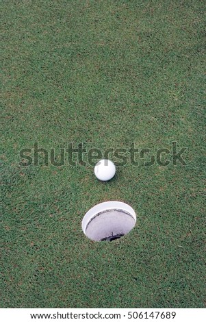 Golf ball and hole are forced Matt to the hole. On the green grass