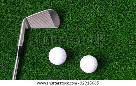 Golf ball and Iron golf club on green fake grass - stock photo