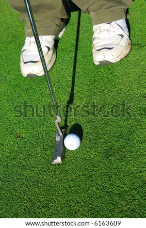 Golf ball and putter on a green - stock photo
