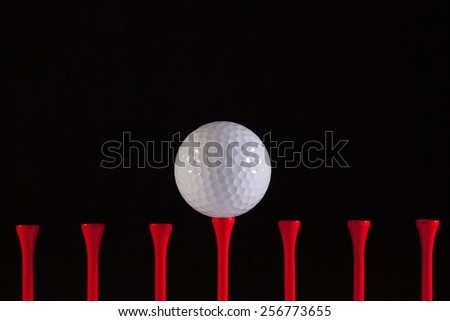 Golf ball and red tee on a black background - stock photo