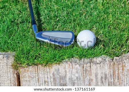 Golf ball and stick inverted wooden support on the grass. - stock photo