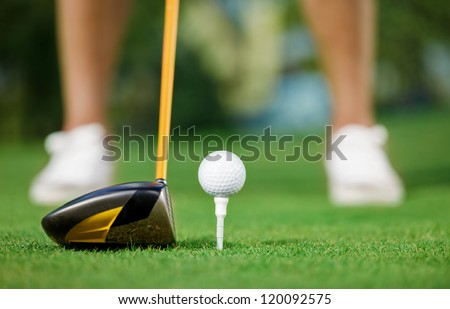 Golf ball and stick with golfer legs in background - stock photo